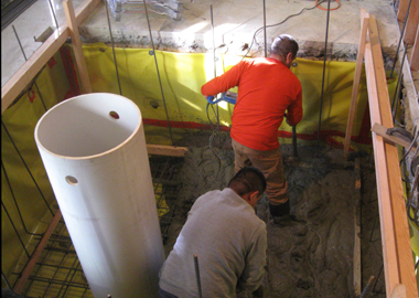 Pouring concrete for the elevator pit floor.