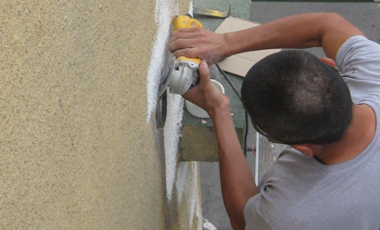 A worker cleans the area around a roof drain.