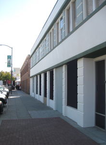 Streamline Moderne building with completed paint along the Court Street façade.