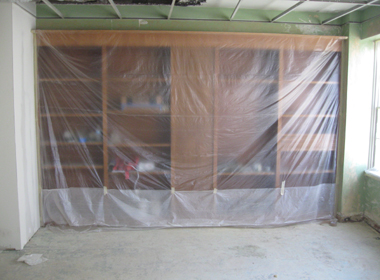 Plastic covering bookcases prior to spraying texture.