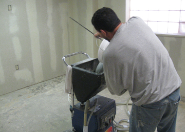 A worker fills the hopper of the texture spraying machine.
