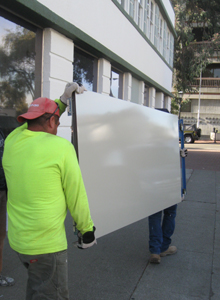Elevator doors are delivered after being painted off site.