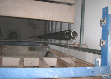 Segments of side rails being stacked up towards the blue bracket on the second story.