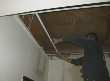 A worker installs more T-Bar to hold ceiling tiles.