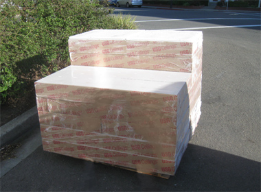 Acoustical ceiling tiles arrive on a pallet.