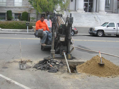 Drilling a horizontal hole under the street and sidewalk for the placement of a conduit.