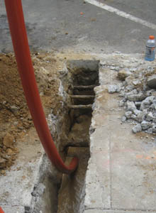 A flexible conduit is pulled through the horizontal hole drilled under the street.
