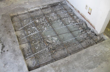After removing an old patch, rebar is dowelled into the adjacent slab to prevent the new patch from raising up.