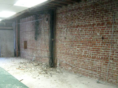Demolition to expose brick wall.