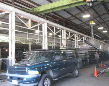 A crane loads a bundle of steel columns onto a pick-up truck.