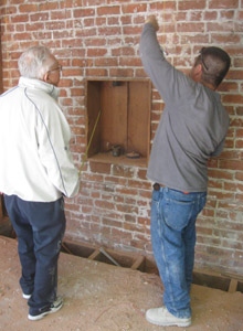Engineer Marvin Kinney inspects a hole drilled in a brick wall.