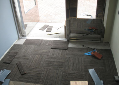The final row of carpet squares being installed in the elevator lobby.
