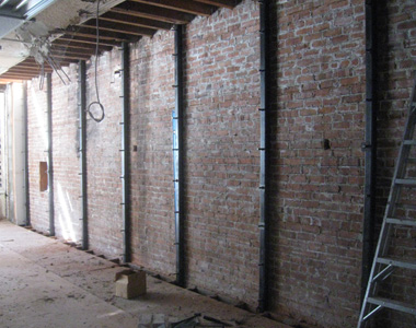 A group of steel columns installed along a brick wall.