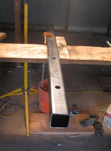 A short steel column sits on a fabrication bench.
