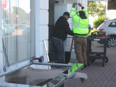 A crew replaces one of the mirror finish doors that had been mismanufactured.
