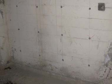 Holes drilled into the basement wall where steel rebar will be epoxied.
