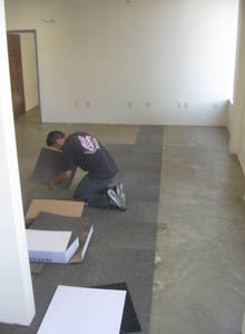 A worker lays carpet tiles.