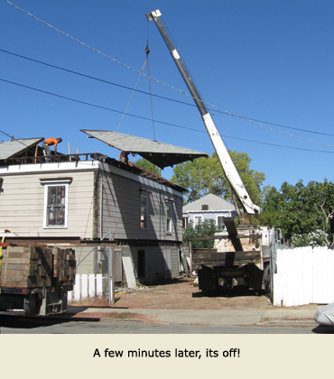 Section of roof being lifted as a part of moving the house.