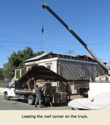 To move the house, a part of the roof is loaded on a Trost Jacking and Heavy Moving truck.