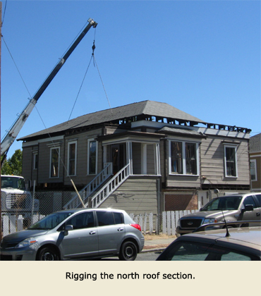 The crane gets ready to lift another part of the roof during the house moving in Martinez, California.