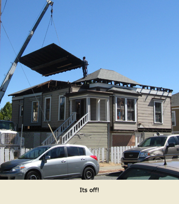 Moving a house in Martinez, California: A section of roof is lifted with a crane.