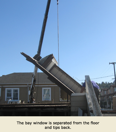 The crane from Trost Jacking of Concord, CA, tips back the bay window during the house moving process.